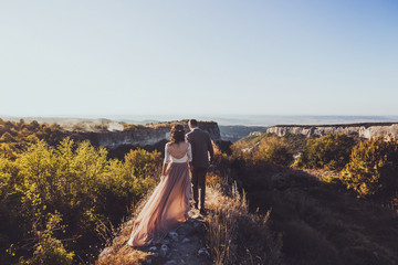 Bride and groom walking in mountains at sunset. Around the stunning canyon