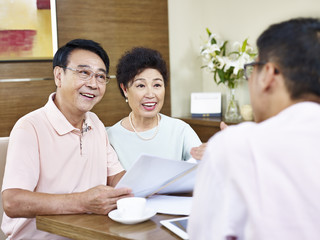 senior asian couple listening to a salesman