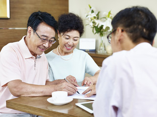 senior asian couple signing a contract