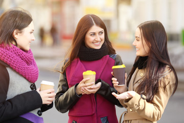 Cheerful young women drinking coffee outdoors