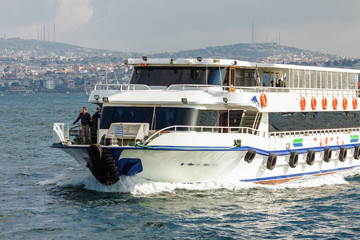 Sunny view of Bosphorus with excursion boat, Istanbul, Turkey.