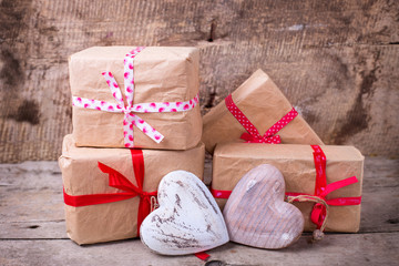 Gift boxes and decorative hearts  on  vintage wooden background.