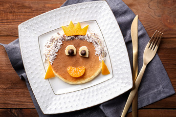 Funny pancake for kids breakfast, on wooden background