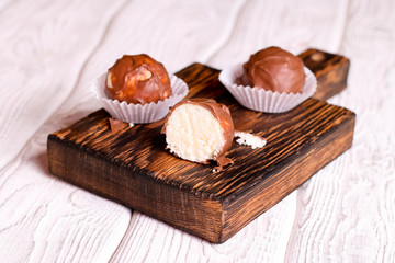 Handmade chocolate coconut candy on wooden table