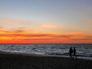 Silhouette couple walking along sunset beach