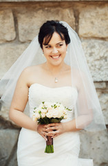 Charming smile of the bride with the beautiful bouquet