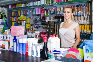 Young female seller standing at pay desk in supermarket