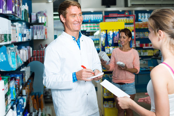 man pharmacist in pharmaceutical shop .