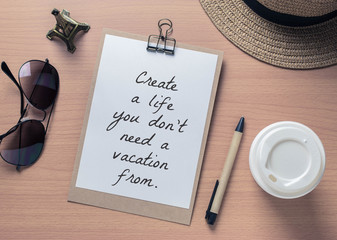 Inspirational motivating quote on notebook and travel objects
