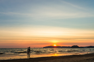 Elderly couple walking on the beach against the backdrop of a beautiful sunset