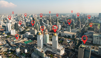 Searching location on map and pin above blue tone city scape and