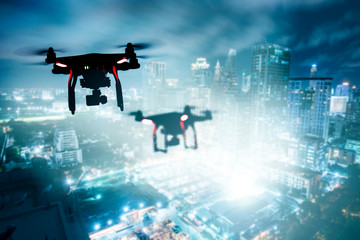 Drone Drone (Multi-rotor) silhouette flying above the city panorama at night scene.