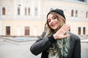 Happy young woman walking on street while waving.