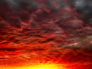 Ein Himmel voller Wolken die von der untergehenden Sonne rot und gelb beleuchtet werden