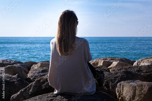 Donna Seduta Di Spalle Sugli Scogli Guarda Il Mare Immagini E