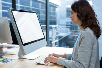 Female graphic designer working over computer at desk