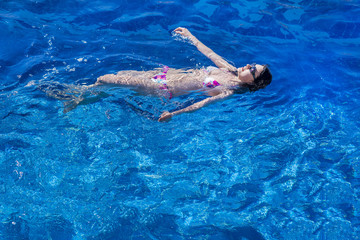 Woman in bikini and sunglasses  swims in the pool