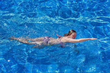 Woman in bikini swims in the pool
