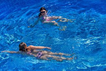 Two women in bikini swims in the pool