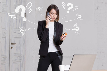 Wall Mural - Business question. Girl in office pays by credit card smartphone business calls.