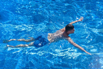 Attractive man swimming in the pool