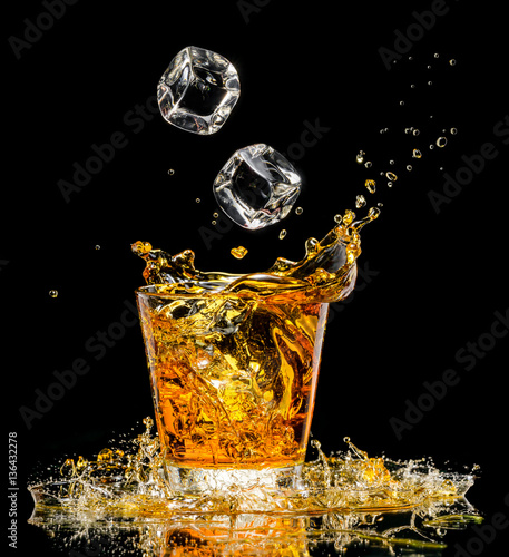 Fototapete Glass of whiskey with splash on black background