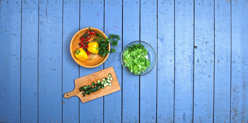Preparation of fresh vegetable salad on blue vintage wooden table. Top view food background.