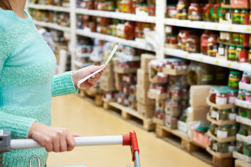 Woman housewife with list shopping in shop