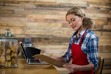 Waitress looking at clipboard while using laptop in café