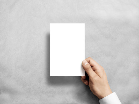 Hand holding blank white vertical postcard flyer mockup. 6 x 4 leaflet mock up presentation. Postal holder. Man show clear post card paper. Sheet template. Invitation booklet reading first person view