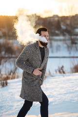 The young guy on the street smoking vape, street fashion with vape steam,vapor e-cigarette