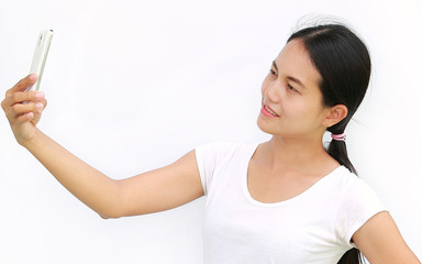 Close up asian girl taking pictures of herself through cell phone on white background