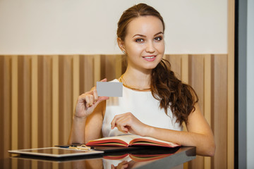 Young female stands near table and holds business card