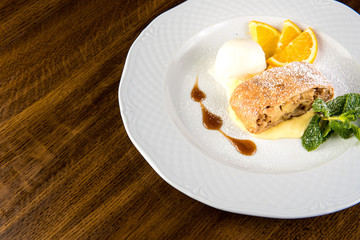 Apple strudel with ice cream and orange on white plate