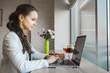 Dark-haired woman typing on laptop. Daylight from window illuminates table