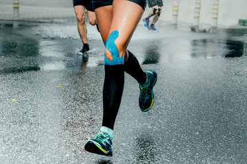 feet girl runners in compression socks and taping on his knees, running on wet asphalt