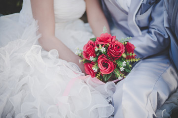 Bride holds a wedding red rose bouquet in hands, the groom hugs
