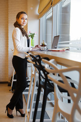 Lovely woman in business suit standing near table with laptop