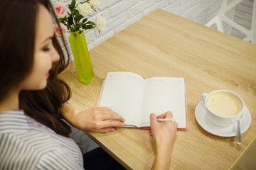 Pretty smiling woman makes entry in her diary on table