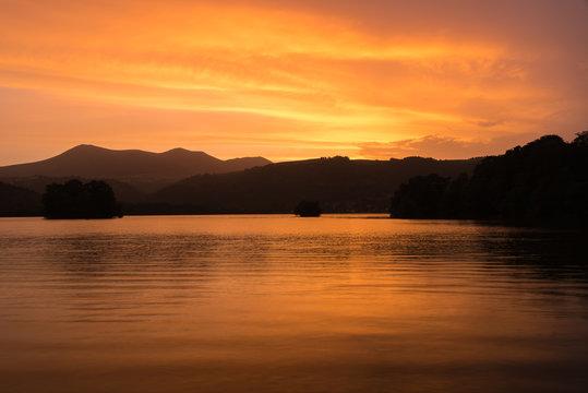 Coucher de soleil en Auvergne autour du Lac Chambon. Nuages oranges et jaunes.