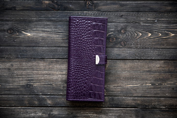 Purlple leather wallet on wooden background top view