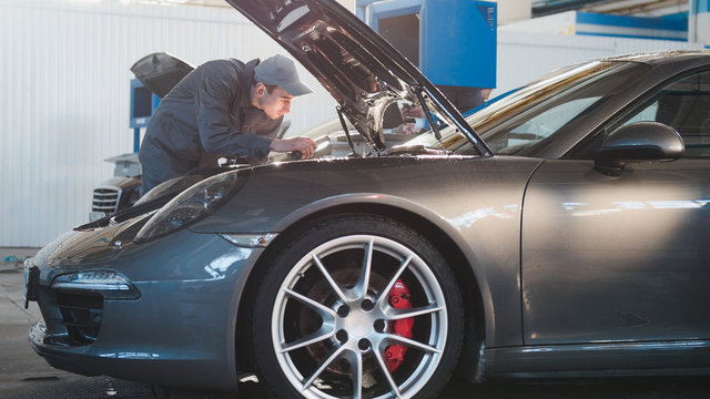 Mechanic male in automobile garage checking hood of the luxury sportcar, telephoto