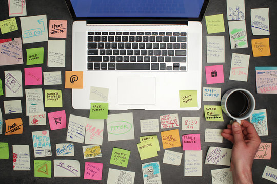 Top view on messy office desk with laptop, coffee and post it notes all around.