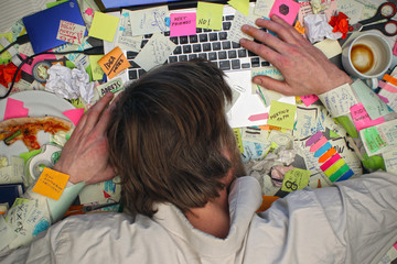 Overworked man sleeping on laptop computer with post it notes all around his office desk.