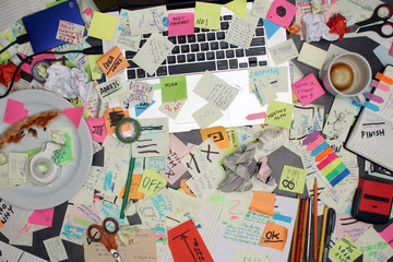 Top view on office desk with laptop computer and post it notes all around. Overwhelmed with work concept. Wall mural