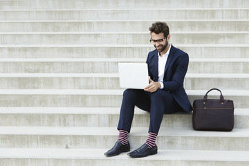 Businessman on laptop with briefcase on steps