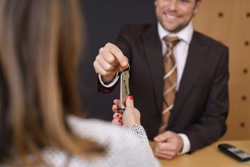 lächelnder rezeptionist im hotel überreicht einem gast den zimmerschlüssel