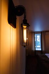 Lantern in interior. Vintage lamp against window, lighting decor. Selective focus.