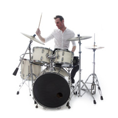drummer behind drum set wears white shirt and plays the drums