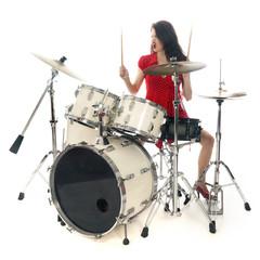 sexy brunette in red dress plays drum kit in studio